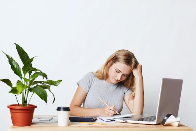 Horizontaal portret van ernstige blonde jonge onderneemster die met potlood in haar notitieboekje kijkt, cijfers berekent, jaarverslag voor haar eigen bedrijf maakt, die laptop computer voor haar werk gebruikt