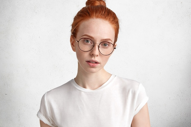 Horizontaal portret van ernstige roodharige vrouw in grote ronde bril kijkt met mysterieuze uitdrukking rechtstreeks in de camera