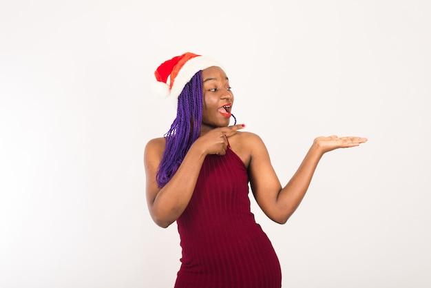 Horizontaal portret van gelukkig donker gevild gemengd ras vrouwelijk model in de kerstman hoed
