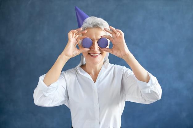 Horizontaal portret van gelukkig grijsharig gepensioneerd kaukasisch wijfje in wit overhemd en kegelhoed die twee ronde amandelkoekjes bij haar ogen houdt
