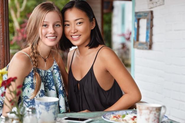 Horizontaal portret van gelukkige vrouwen van verschillende nationaliteiten rusten goed in café, poseren samen bij tafel met heerlijk gerecht en thee, hebben verrukkelijke blikken.