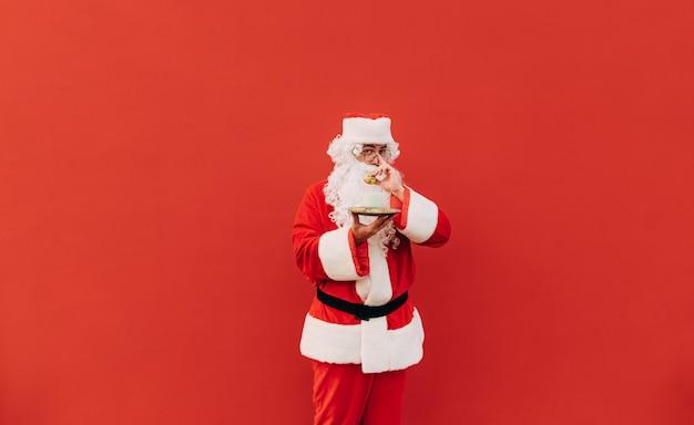 Horizontaal portret van halve lengte van de positieve kerstman die zijn bril aanraakt