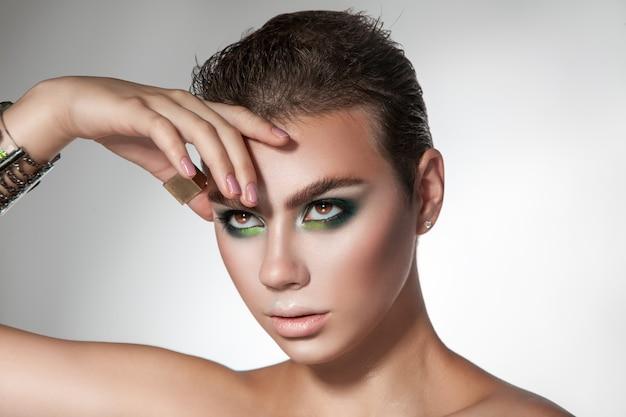 Horizontaal portret van jong schoonheidsmeisje met groene kleurenmake-up en kort kapsel