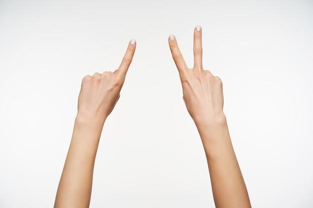 Horizontaal portret van jonge dames met lichte huid, armen met vier vingers terwijl ze het tellen van gebaren op gebarentaal demonstreren, geïsoleerd op wit