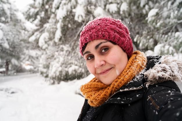 Horizontaal portret van jonge kaukasische vrouw die buiten onder de sneeuw frisse lucht inademen.
