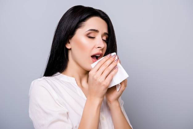 Horizontaal portret van jonge zieke vrouw die in servet niest
