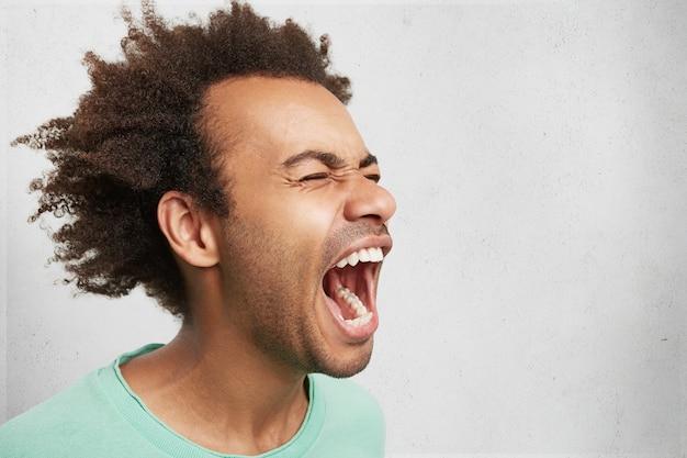 Horizontaal portret van man met donkere huid en afro-kapsel schreeuwt van wanhoop, opent mond wijd, in paniek