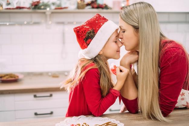 Horizontaal portret van moeder en dochter. een tienermeisje kust haar moeder in de neus in de keuken