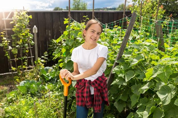 Horizontaal portret van mooi lachend meisje poseren in de tuin met schop