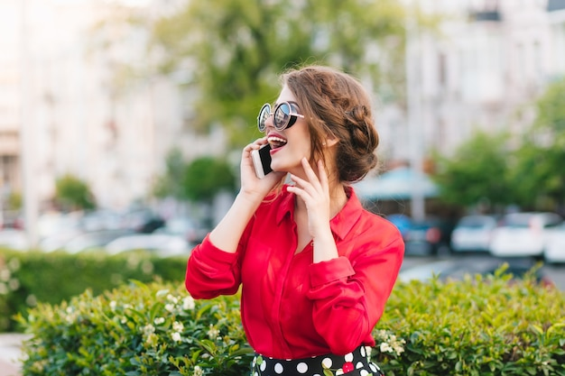 Horizontaal portret van mooi meisje die in zonnebril in park lopen. ze draagt een rode blouse en een mooi kapsel. ze praat aan de telefoon en glimlacht ver weg.