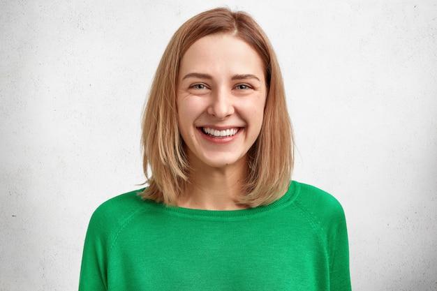 Horizontaal portret van mooi vrolijk jong vrouwelijk model met kortgeknipt kapsel, prettige zachte glimlach, gezonde huid, draagt groene sweater
