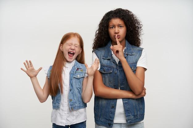 Horizontaal portret van mooie jonge donkerhuidige brunette vrouw met wijsvinger op haar lippen en vraagt om stilte te houden, staande op wit met opgewonden foxy klein meisje