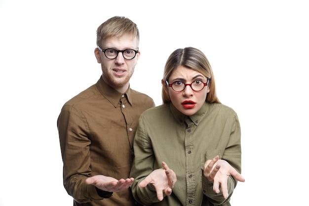 Horizontaal portret van onwetende jonge blanke man en vrouw die verwarde gebaren maken terwijl ze samen poseren, zoekend naar woorden, verontwaardigd en geïrriteerd kijken