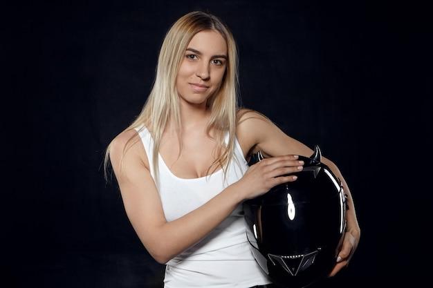 Horizontaal portret van positief jong europees atletisch wijfje met geverfd haar dat wit mouwloos onderhemd draagt