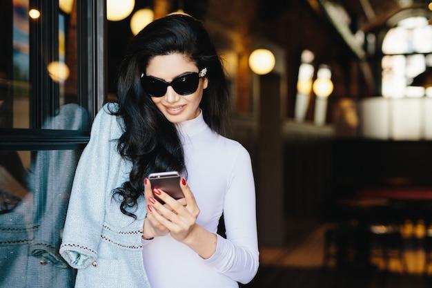 Horizontaal portret van prachtige donkerbruine vrouw in witte kleren en zonnebril die in koffie zitten die haar smartphone gebruiken