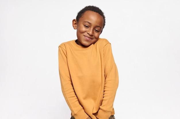 Horizontaal portret van schattige knappe donkere huid kleine jongen schouderophalend gevoel in verlegenheid gebracht met een ongemakkelijke vraag