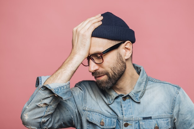 Horizontaal portret van stressvolle stijlvolle ongeschoren man betreurt iets, houdt hand op hoofd