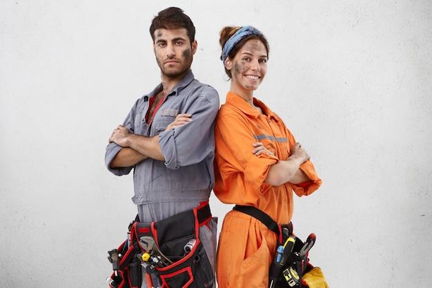 Horizontaal portret van succesvolle hardwerkende jonge vrouwelijke en mannelijke technici werken als vriendelijk team