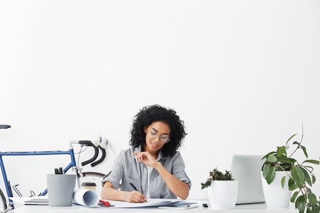 Horizontaal portret van succesvolle jonge donkere ingenieursvrouw die casual overhemd draagt