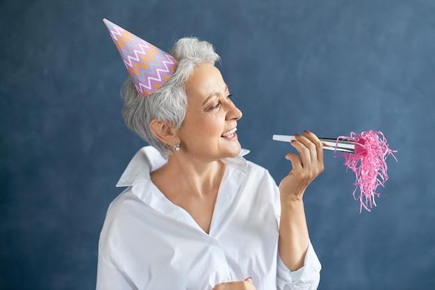Horizontaal portret van succesvolle zekere vrouw van middelbare leeftijd in wit overhemd en speelse kegelvormige noisemaker van de hoedenholding
