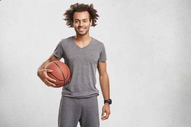 Horizontaal portret van terloops gekleed basketbalspeler, houdt bal vast,