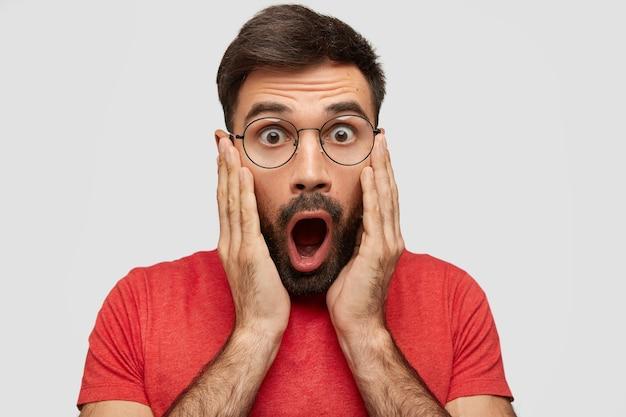 Horizontaal portret van verbaasde bebaarde man raakt wangen met handen, staart met afgeluisterde ogen, voelt zich verbaasd en verrast, hoort iets vreselijks, gekleed in een rood casual t-shirt. reactie concept