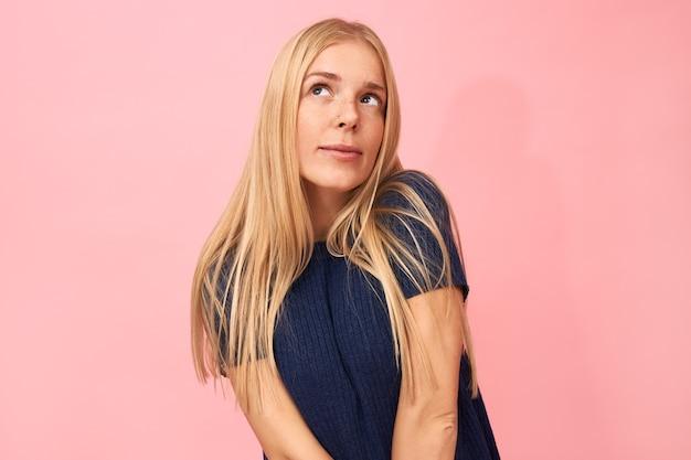 Horizontaal portret van verlegen jonge vrouw met blonde losse haren opzoeken met peinzende gezichtsuitdrukking