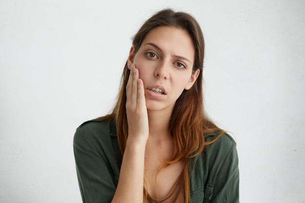 Horizontaal portret van vrij droevige vrouw met heldere donkere ogen en steil haar die hand op wang houden die boos kijken