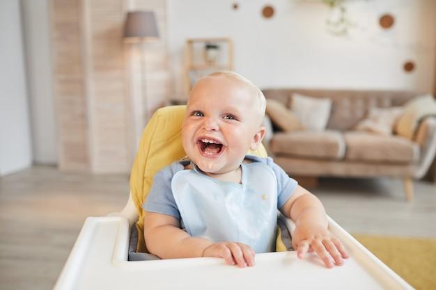Horizontaal portret van vrolijk klein kind zittend op een hoge stoel met voedsel rond zijn mond glimlachen