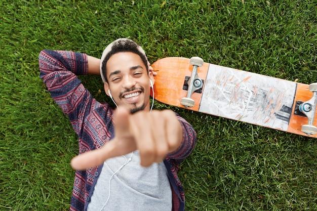 Horizontaal portret van vrolijke bebaarde mannelijke skateboarder ligt op groen gras in de buurt van skateboard, luistert naar muziek met koptelefoon
