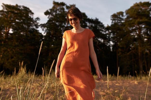 Horizontaal portret van vrolijke jonge brunette vrouw draagt een zonnebril en katoenen rode jurk poseren buitenshuis met vrolijke glimlach