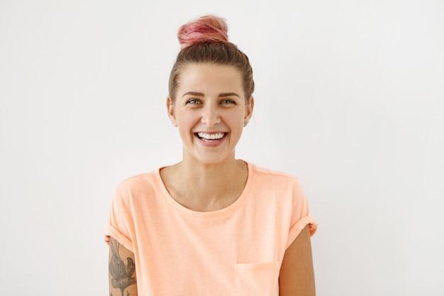 Horizontaal portret van vrolijke vrouw met aantrekkelijke glimlach, met roze haarknotje en tatoeage, casual kleding dragend,