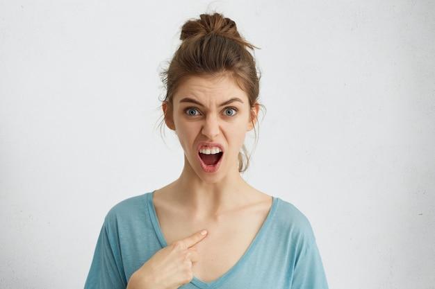 Horizontaal portret van woedende jonge vrouw met blauwe ogen die wijd geopende mond van woede hebben die naar zichzelf richt met vinger die haar wenkbrauwen fronst. heb ik het gedaan? mensen en emoties concept