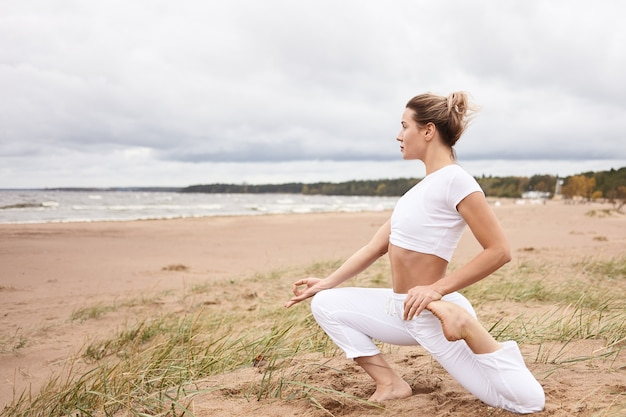 Horizontaal profiel van mooie atletische jonge blonde vrouw trainen op zandstrand, met uitzicht op zee, warming-up rekoefeningen doen tijdens yoga beoefening, zittend in eka pada rajakapotasana