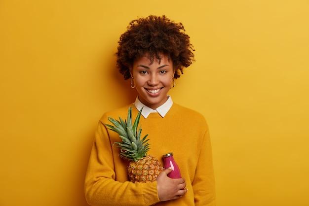Horizontaal schot van aangenaam uitziend gelukkig meisje met afro-kapsel, houdt rijpe ananas en smoothie, poseert met exotisch fruit, heeft brede brede glimlach, directe blik, geïsoleerd op gele muur