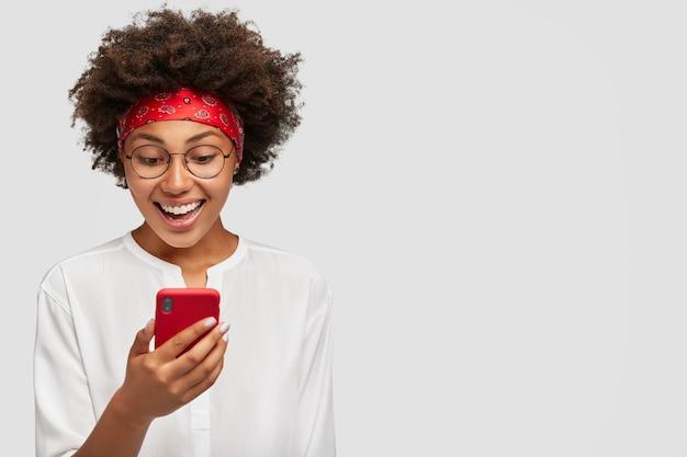 Horizontaal schot van aangenaam uitziende zwarte volwassene, opgewonden met videochat, bijgewerkte mobiele telefoon bij zich, heeft een brede glimlach