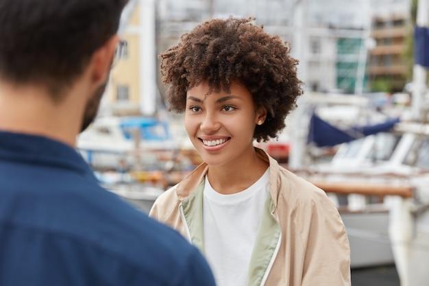 Horizontaal schot van aantrekkelijk afro-amerikaans meisje heeft een prettige uitstraling, brede glimlach