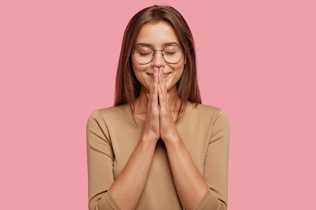 Horizontaal schot van aantrekkelijke tevreden vrouw bidt voor goed welzijn, houdt de handpalmen tegen elkaar gedrukt