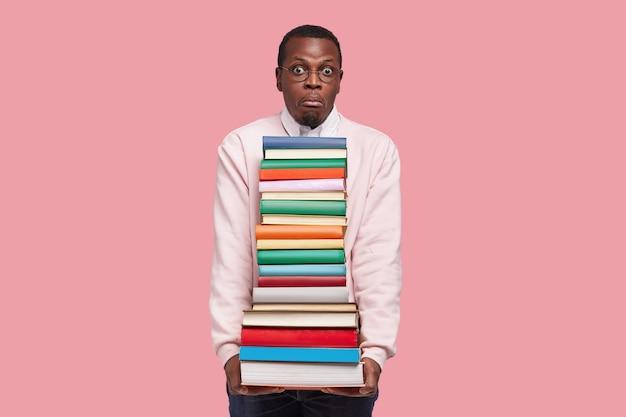 Horizontaal schot van afro-amerikaanse student heeft uitdrukking, verbaasde blik verbaasd, bevat dikke encyclopedie en wetenschappelijke literatuur