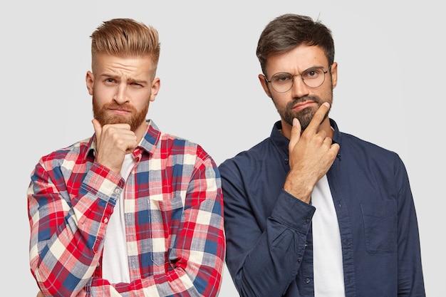 Horizontaal schot van beste mannelijke vrienden hebben geen idee van uitdrukkingen, houden hun kin vast, denken na en nemen belangrijke beslissingen