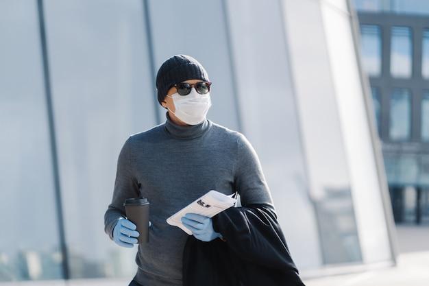Horizontaal schot van blanke man gekleed in coltrui en hoed, trekt jas uit, draagt beschermend medisch masker en rubberen handschoenen tijdens epidemische situatie, drinkt koffie en houdt verse krant vast