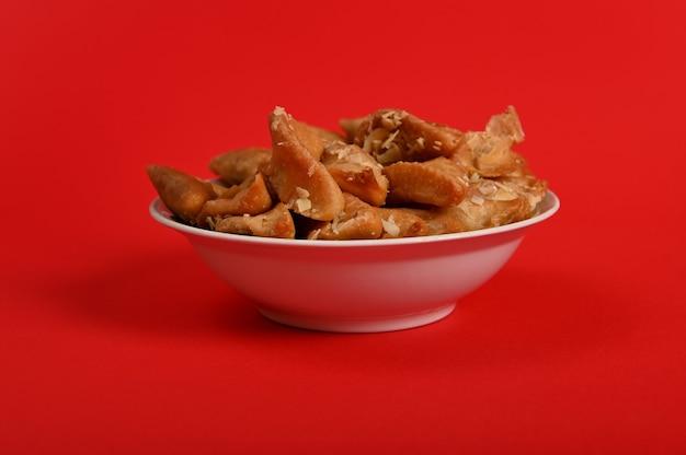 Horizontaal schot van bord vol verse traditionele luxe arabische handgemaakte brewat-snoepjes, geïsoleerd op rode achtergrond. arabische traditionele oosterse zoetigheden op de feesttafel
