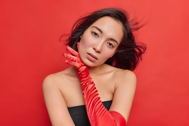 Horizontaal schot van charmante aziatische vrouw met natuurlijke schoonheid raakt het gezicht zachtjes aan, heeft donker haar dat in de lucht zweeft en draagt zwarte jurk lange handschoenen geïsoleerd over een levendige rode muur