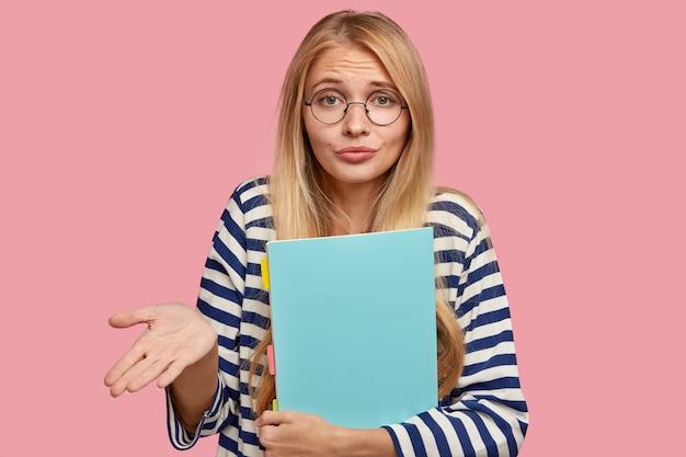 Horizontaal schot van clueless blonde vrouw grijpt handpalm met aarzeling, draagt een ronde transparante bril