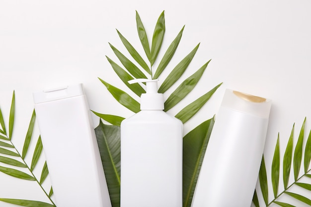 Horizontaal schot van cosmetische producten tegen groen of bladeren.