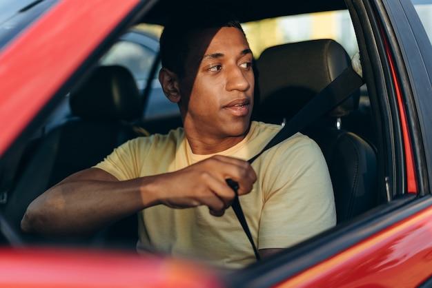 Horizontaal schot van de jonge multiraciale man die veiligheidsgordels vastmaakt terwijl hij zit en zich voorbereidt op het rijden met de auto op de weg. vervoersconcept: