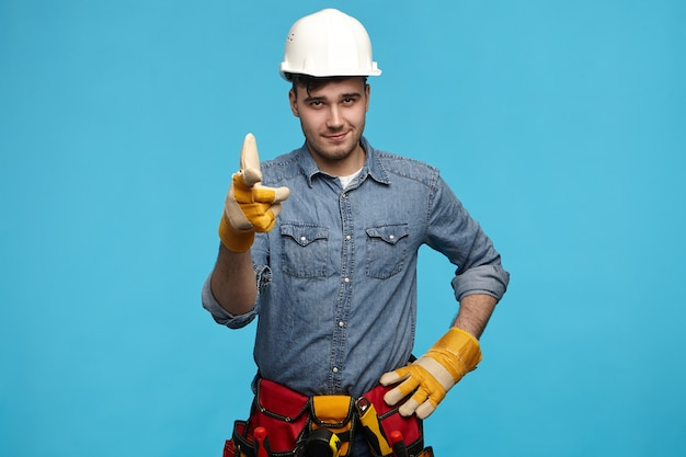 Horizontaal schot van de knappe jonge werknemer van de onderhoudsdienst die witte helm draagt
