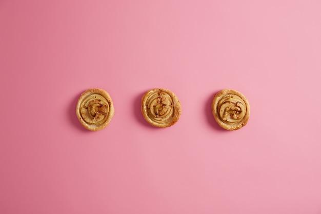 Horizontaal schot van de verse zelfgemaakte broodjes van de wervelingskaneel die op roze achtergrond worden geïsoleerd. zoetekauw, verleiding en junkfood-concept. lekker dessert. dieet doorbreken. heerlijke suikerbroodjes.