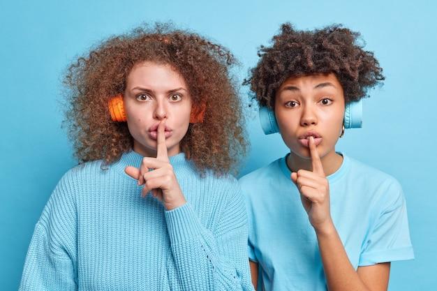 Horizontaal schot van diverse tienermeisjes die zeggen dat ze stil moeten zijn, maak een stil teken om informatie in het geheim te bewaren, kijk mysterieus gekleed en luister nonchalant naar muziek via een koptelefoon geïsoleerd over blauwe muur
