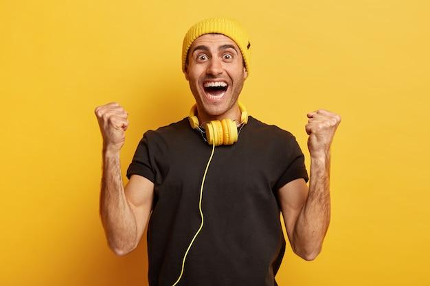 Horizontaal schot van dolgelukkig gelukkig man balde vuisten, voelt als winnaar, in hoge geest